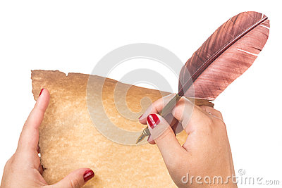 Female hand writing on old paper scroll and fountain pen with feather quill isolated on white background.
