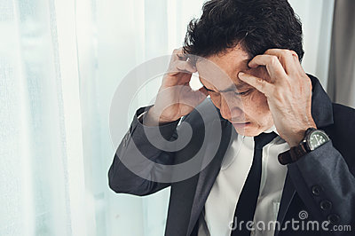 Asian businessman has headache from migraine from overworked. Il