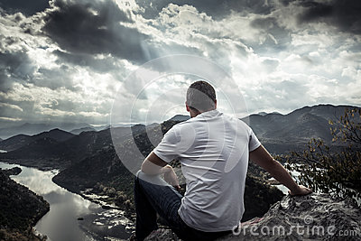 Lonely man looking with hope at horizon on mountain peak with dramatic sunlight during sunset with effect of light at the end of t