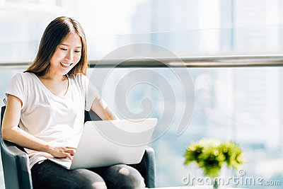 Beautiful Asian girl using laptop computer. College student or freelance worker in modern office. Education or business concept