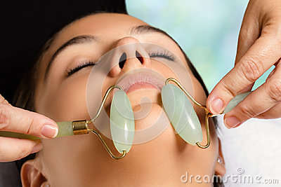 Facial beauty treatment with jade rollers.