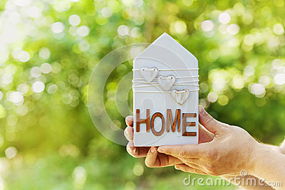 Male holds in hands house decorated hearts on green bokeh background. Real estate, buying a new home, insurance, sun energy, eco.