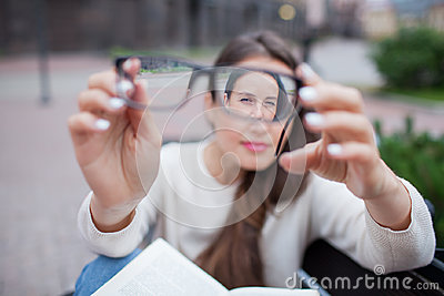 Closeup portrait of young women with glasses. She has eyesight problems and is squinting his eyes a little bit. Beautiful girl is