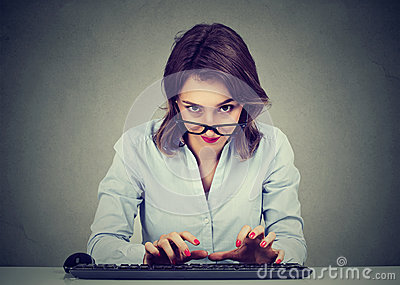 Crazy looking nerdy young woman typing on the keyboard wondering what to reply
