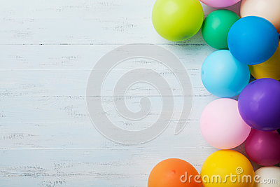 Heap of colorful balloons on blue wooden table top view. Birthday or party background. Flat lay style. Copy space for text.