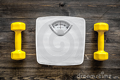 Fitness for losing weight. Bathroom scale and dumbbell on wooden background top view
