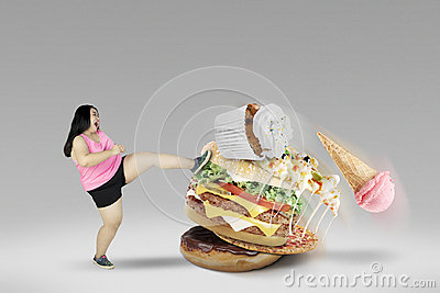 Young female kicking unhealthy foods