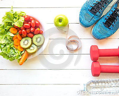stock image of healthy lifestyle for women diet with sport equipment, sneakers, measuring tape, vegetable fresh, green apples and bottle of water