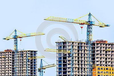Two multi-storey buildings under construction. Many cranes. Construction of modern housing.