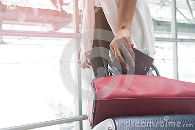 Close up of woman hand holding passport and dragging luggage suitcase