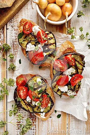 Bruschetta with grilled eggplant, cherry tomatoes, feta cheese, capers and fresh aromatic herbs on a wooden table. Delicious Medit
