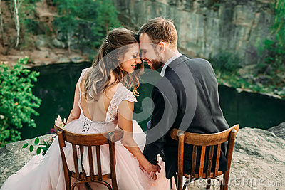 Newlyweds sitting at the edge of the canyon and couple looking each other with tenderness and love. Bride and groom