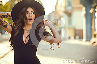 Gorgeous glam tattooed lady holding her trendy fedora hat for it not to be blown away, her mouth open with surprise