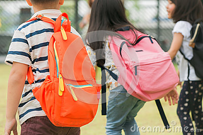 Three pupils of primary school go hand in hand. Boy and girl with school bags behind the back. Beginning of school lessons.