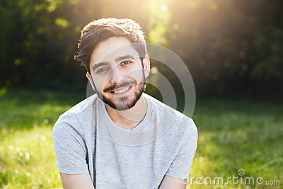 Young smiling man with dark hair, thick eyebrows, appealing eyes and beard wearing casual T-shirt sitting at greenland having good