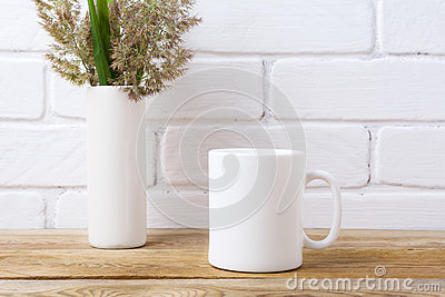 White coffee mug mockup with grass and green leaves in cylinder