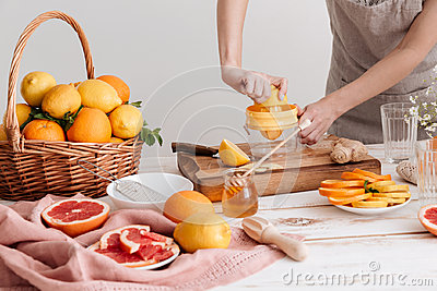 Cropped picture of woman squeezes out juice of a citruses.