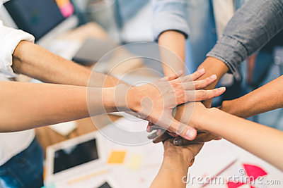 stock image of business partners teamwork or friendship concept. multiethnic diverse group of colleagues join hands together