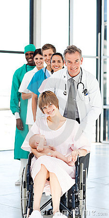 Doctors attending to a patient and her baby