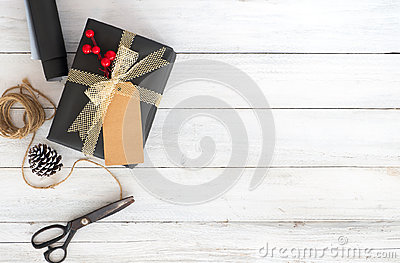 Hand crafted Christmas present gift box and tools on white wooden background.