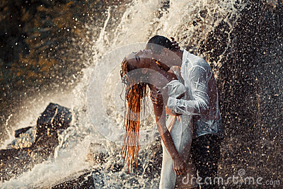 Young enamored couple hugs and kisses under spray of waterfall.
