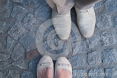 Man and woman face to face stand on cobbles. Focus on the footwear.