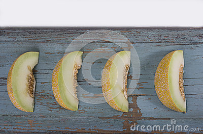 Slices of fresh yellow melon or cantaloupe on the olg grungy wo