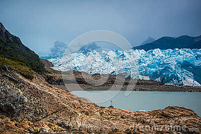 Beautiful landscape of a blue glacier and mountains with a bay. Shevelev.
