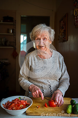 An elderly happy woman chops vegetables for a salad in the kitchen.
