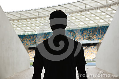 Silhouette of a man standing at the stadium