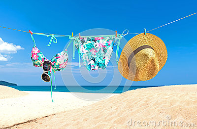 Fashion summer swimsuit bikini, sunglasses and big hat on rope. Summer bikini and accessories stylish outfit beach set. Ocean sea