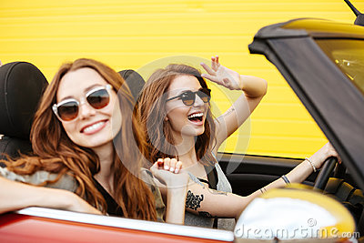 Happy two women friends sitting in car over yellow wall.