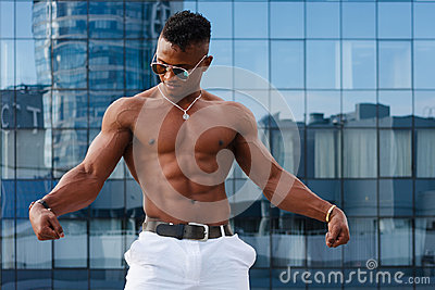 Hot Beautiful black guy with bulging muscles posing against the backdrop of the urban landscape. Man fitness model.