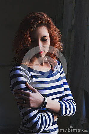 Dramatic portrait of a young beautiful girl. A girl with a pleasant appearance and sad look. Creative portrait of a woman.