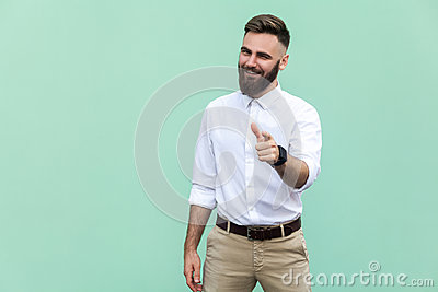 Hey you! Young adult bearded man, pointing finger and looking at camera. On light green background. Indoor