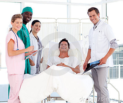 Doctors attending to a patient smiling at the came