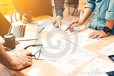 Brainstorming team of asian startup coworkers doing work on desk