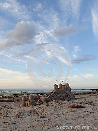 Big sandcastle on mound with moat, & cloudy blue  sky.