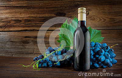 A bottle of red wine with a vine grape