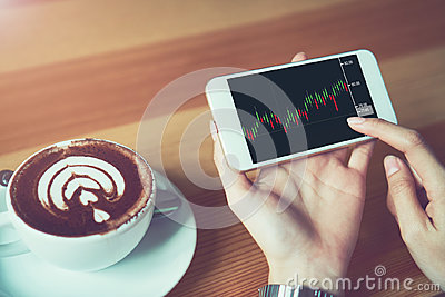 The woman holds the phone on a table with a graphical screen to invest the stock`s value. Investment concepts that rely on decisi