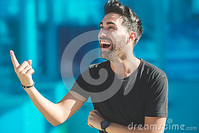 Young happy man pointing up laughing