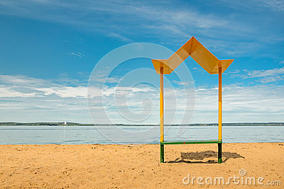 Empty beach with a bench with a canopy on the coast
