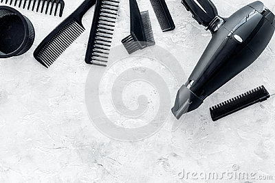 Hairdresser working desk with dryer and tools for hair styling on gray stone desk background top view mock up