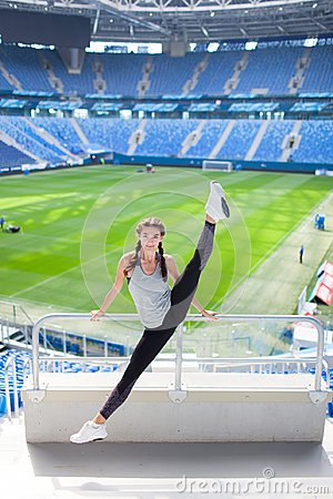 stock image of young sporty girl jumped high and spread her legs in different directions on the background of a football stadium. woman in sports