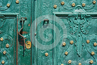 Old iron door, forged and painted in green color with golden flowers for background, vintage style, retro elements