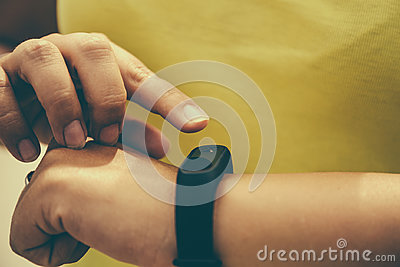 Girl checks pulse on fitness bracelet or activity tracker pedometer on wrist, sport, technology and healthy lifestyle concept