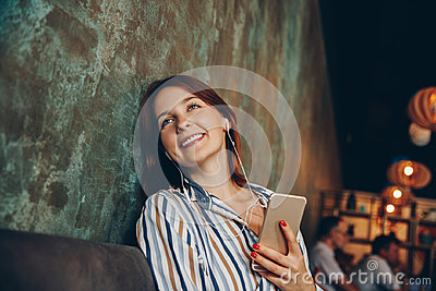 Young woman listen music with headphones and relaxing. Sitting on cafe, domestic atmosphere. Positive emotion,closed eyes, loft i