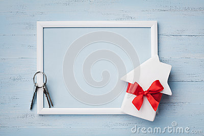 House with ribbon, frame and keychain on wooden background. Buying a new home, planning housewarming, gift or sale of real estate