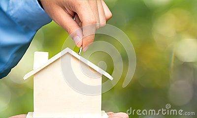 Male hand holding coins and piggy house bank save money, green nature background. Investment and save Concept.