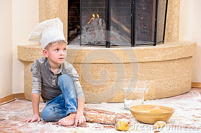A boy in chef`s hats near the fireplace sitting on the kitchen floor soiled with flour, playing with food, making mess